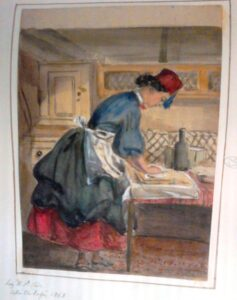 Colour image of a lady preparing baking ingredients on a table, and most notably with a fez!